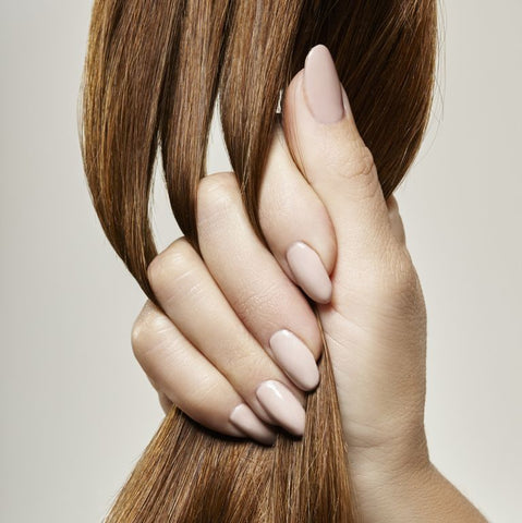 A hand grabbing healthy brown hair
