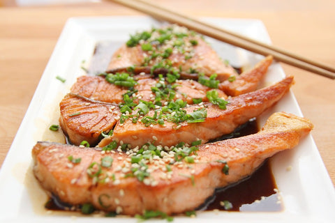three pieces of fatty fish that is high in Omega-3 with teriyaki sauce on a plate with chopsticks