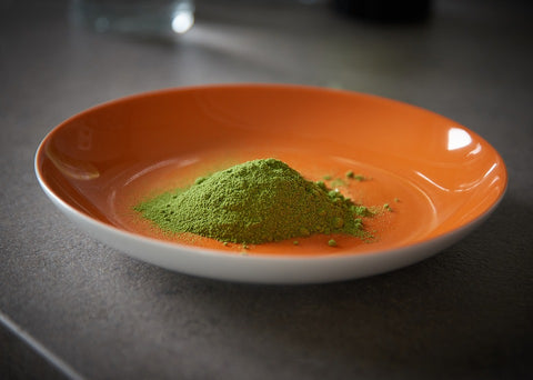 Moringa powder in a orange coloured plate