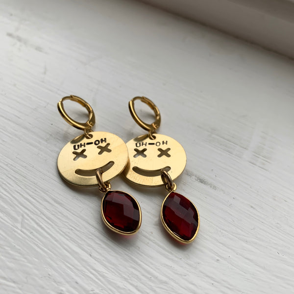 """Uh-Oh"" Smiley Stamped Crystal Earrings - Garnet"
