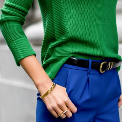 Lady wearing blue trousers with a black belt and green sweater