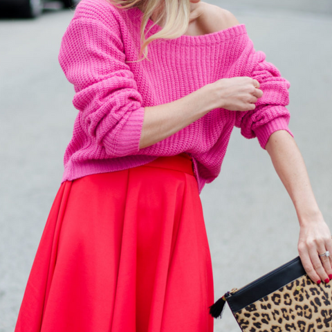 Lady wearing pink knitted sweater and red pleated skirt with leopard print clutch bag