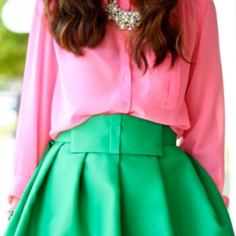 Lady wearing a pink blouse and green pleated skirt