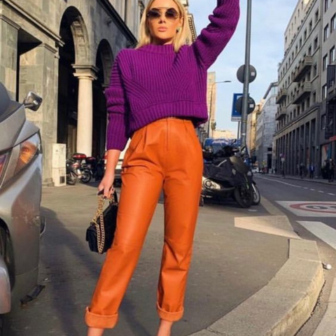 Lady wearing leather orange trousers with a purple knitted sweater