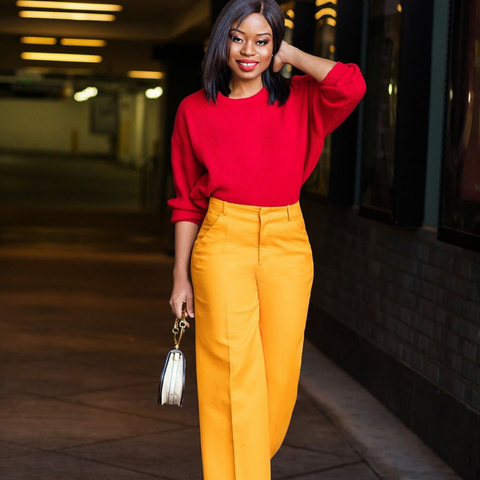 Lady with high waisted yellow trousers and red knitted sweater