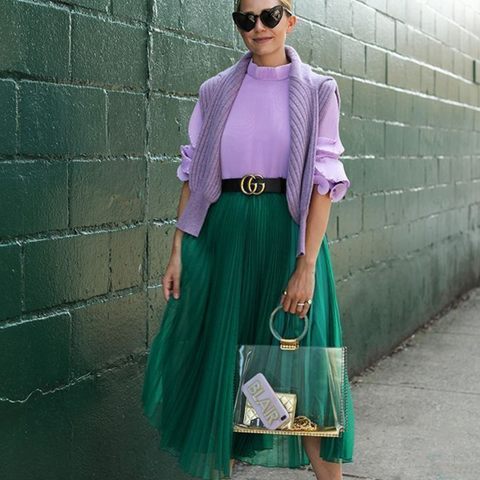 Lady wearing a green skirt and lilac purple knitted sweater