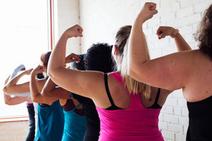 strong women in yoga tops flexing biceps