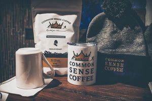"Common Sense Coffee's freshly roasted Washington Medium Roast next to the Common Sense tumbler and classic ""Beanie"" hat. Common Sense Coffee specializes in the single origin specialty market by offering high-quality coffee to people who change the world."