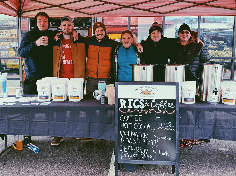 The Common Sense Coffee Team posing for a group photo behind the booth at the January 4, 2020 Rigs & Coffee event. Common Sense Coffee is a single origin coffee subscription service that focuses on providing coffee to people who are changing the world.