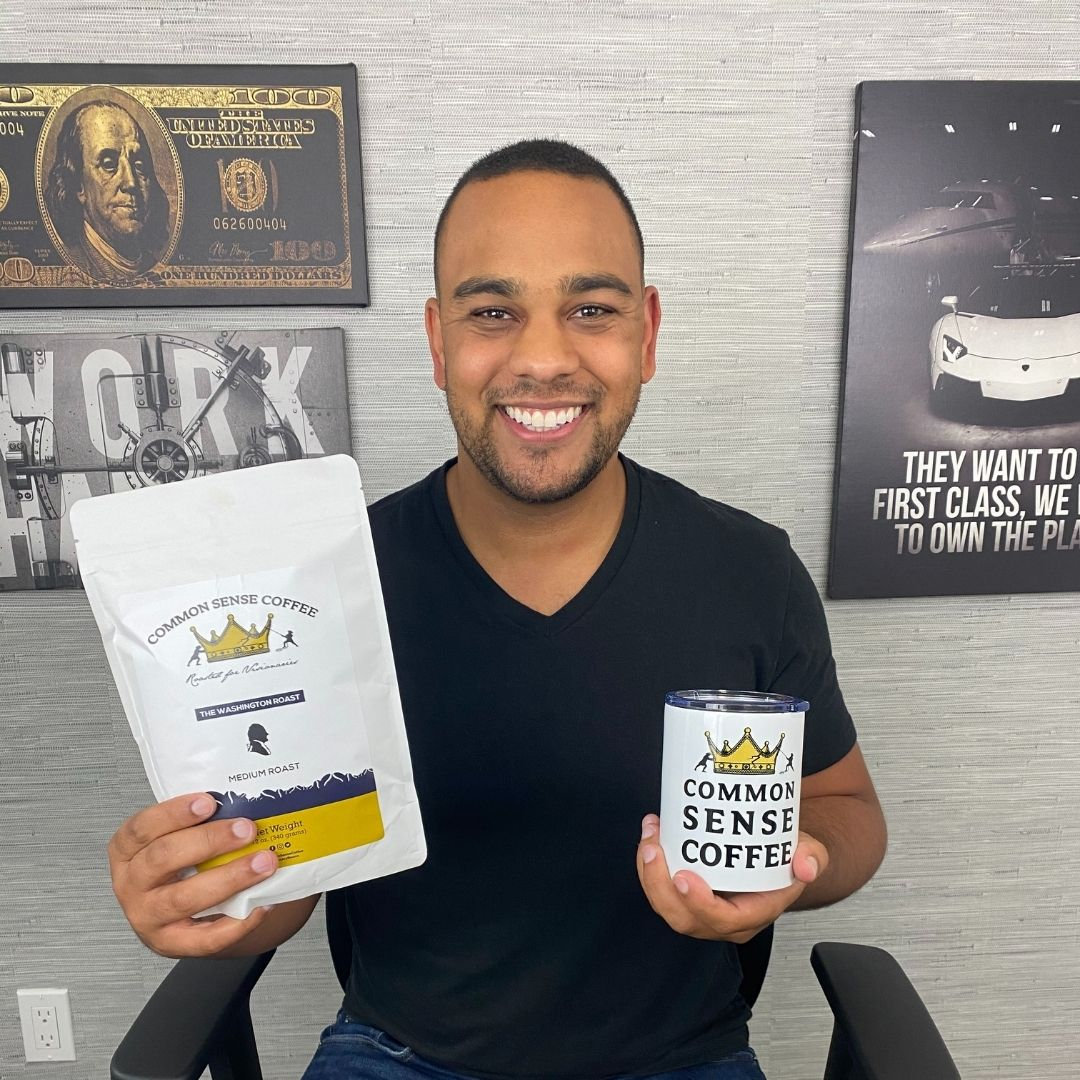 Todd Baldwin smiles holding his brand new Common Sense Coffee Tumbler and Washington Medium Roast in his brand new YouTube studio in Burion, Washington. Todd is a millionaire real estate investor and YouTuber that teaches all areas of personal finance to the world.