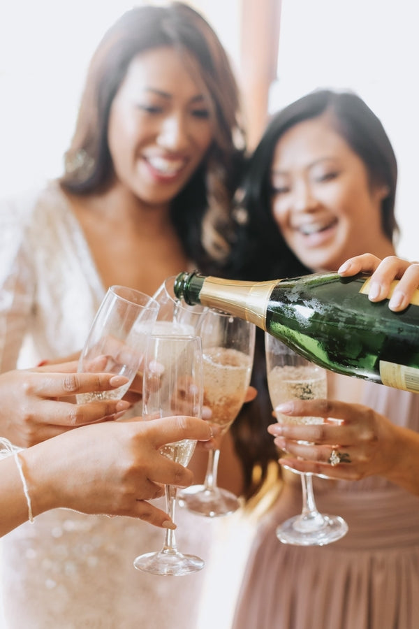 Bride and Bridesmaids Pouring Champagne | A Dazzling Doughnut Wedding | Kate Aspen