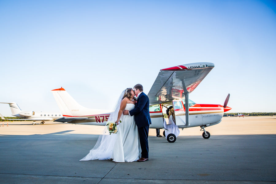 Bride and Groom Kiss In Front Of Airplane | Aviation Themed Wedding | Red Bridge Photography