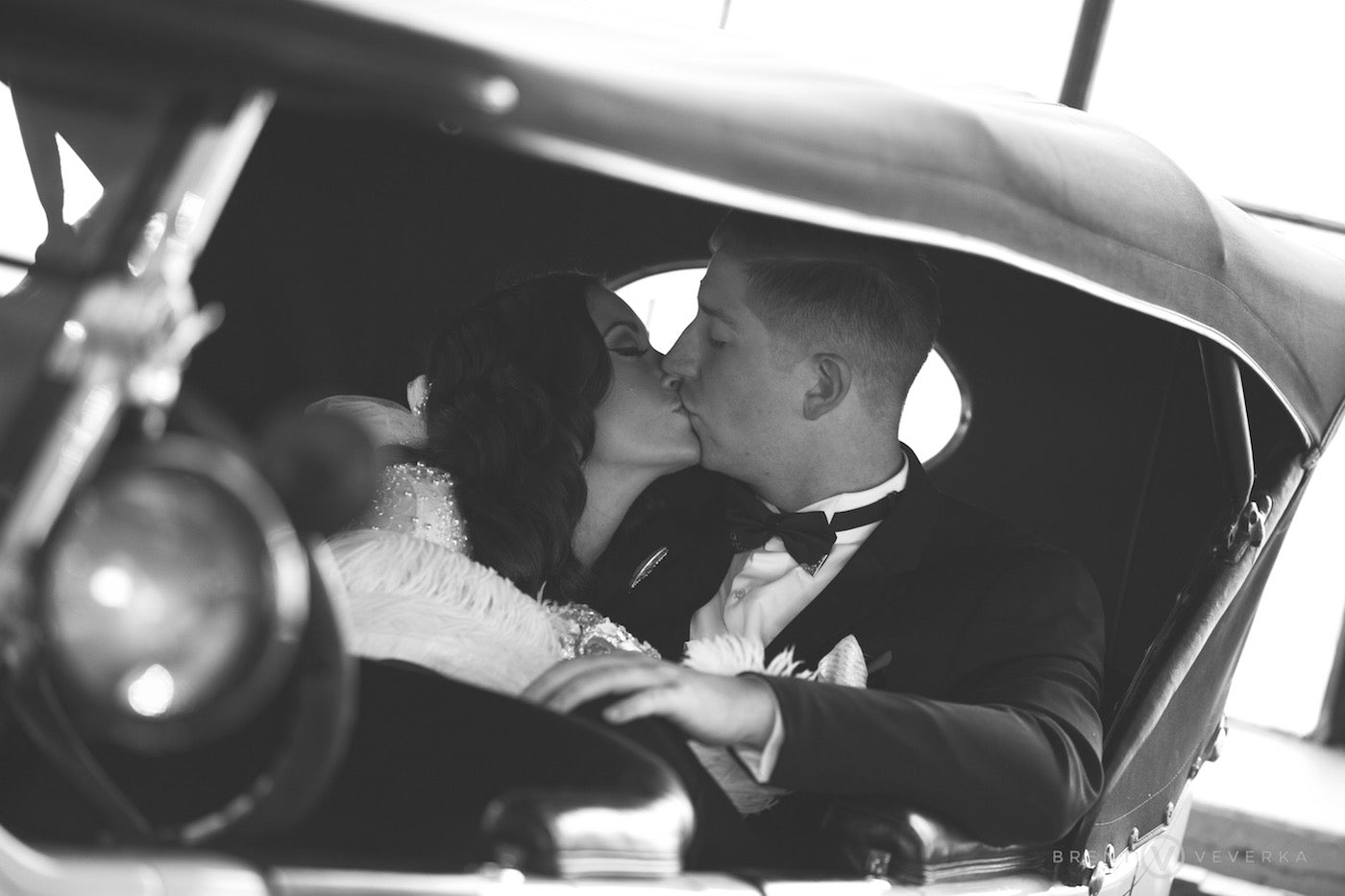Bride and Groom Kiss in Antique Car | Glam Speakeasy Wedding | Brent Veverka Media