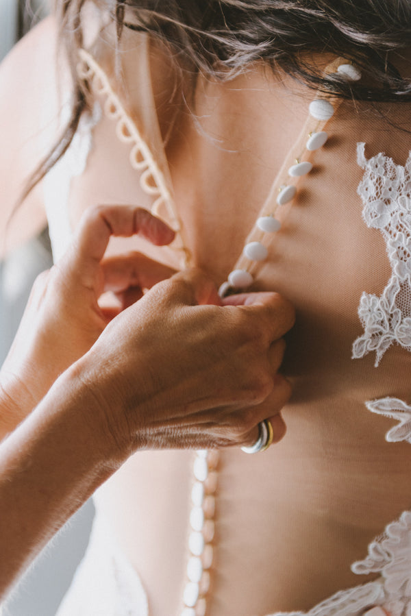 Buttoning the Bride's Dress | Santorini Destination Wedding | Vasilis Lagios Photography