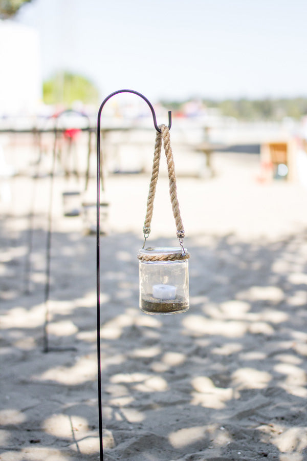 Lanterns on shepherds hooks line the path to a private beach party | Megan Long Photography