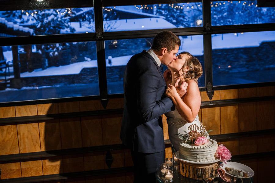 Bride and Groom with Cake | A Snowy Spring Wedding | Kate Aspen