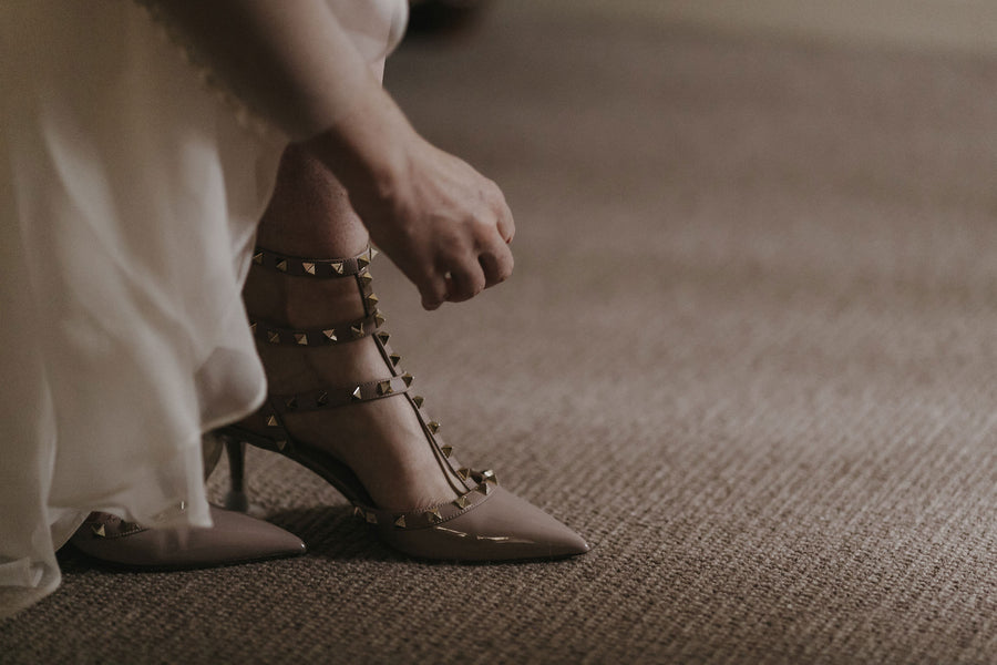 Bride Putting On Her Shoes | A Farmhouse Chic Wedding | Kate Aspen