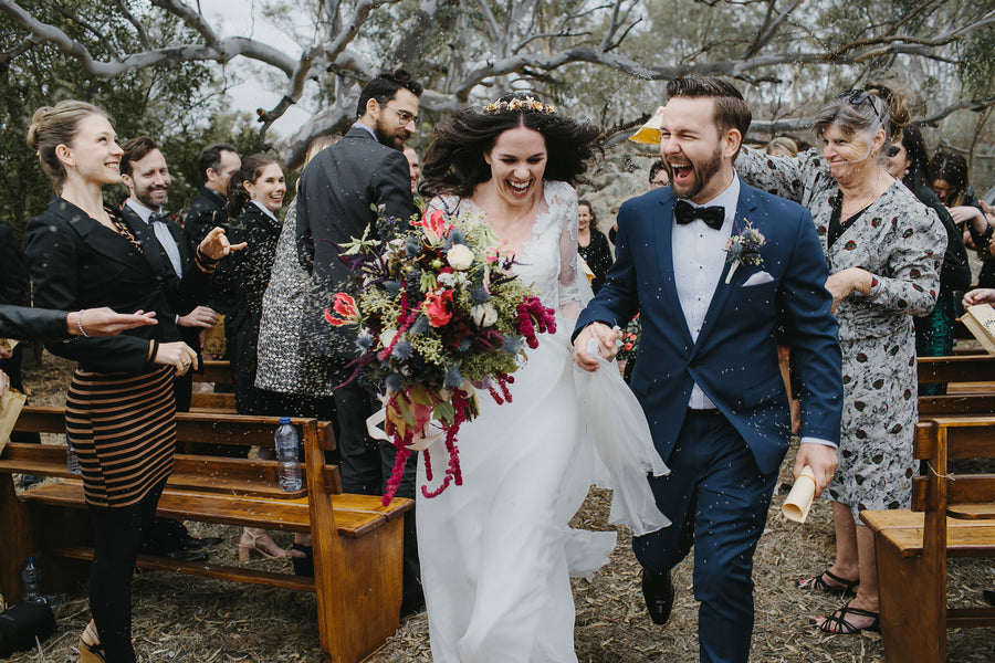 Bride and Groom Exiting with Confetti | A Farmhouse Chic Wedding | Kate Aspen