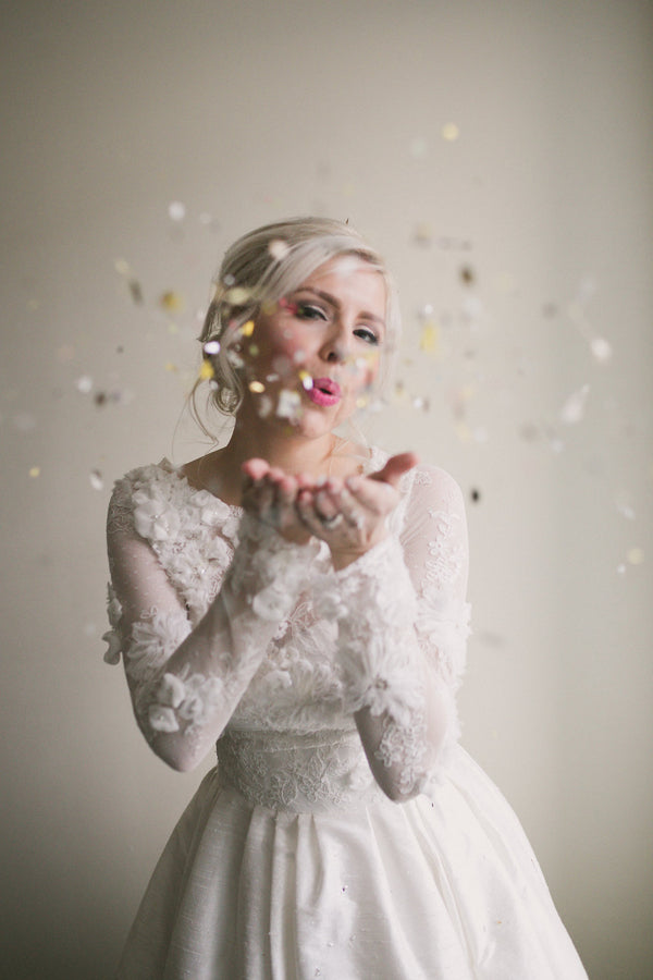 Bride Blowing Confetti | Copyright Ampersand Studios 2014