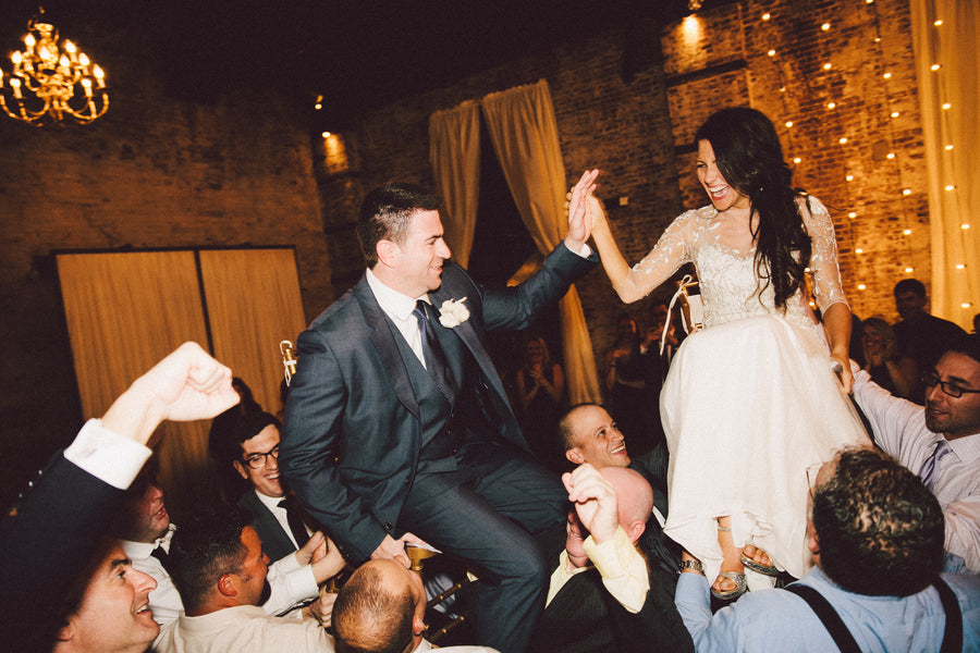 Bride and Groom Lifted in Chairs for Hora | Speakeasy Themed Industrial Wedding | Zorz Studios | @kateaspen