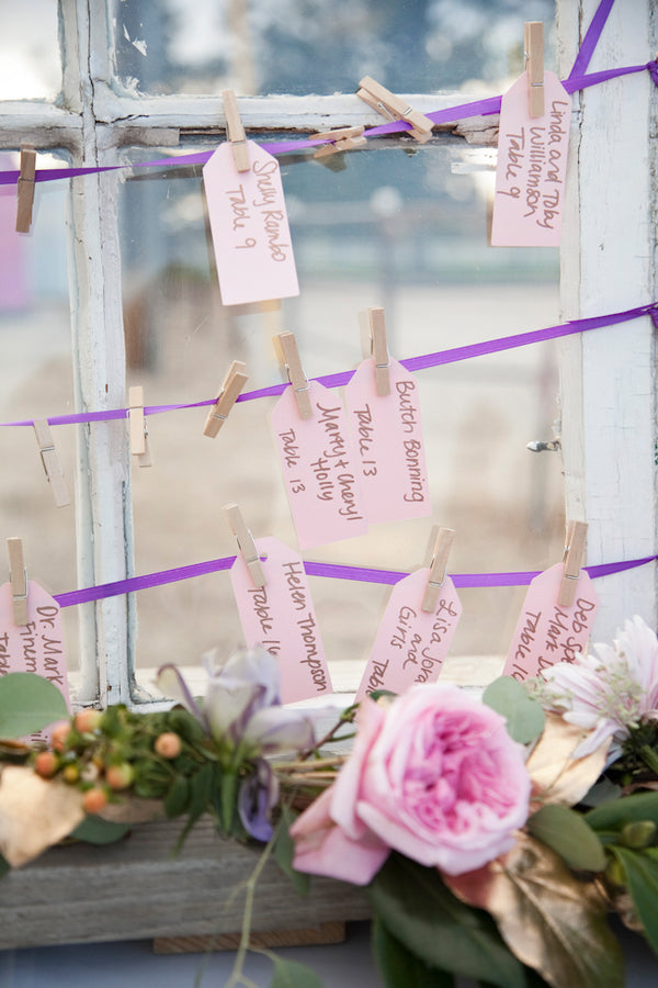 Wedding seating place cards pinned to ribbon with clothespins | Tana Photography