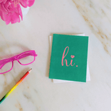 "Green ""hi."" greeting card on marble counter"