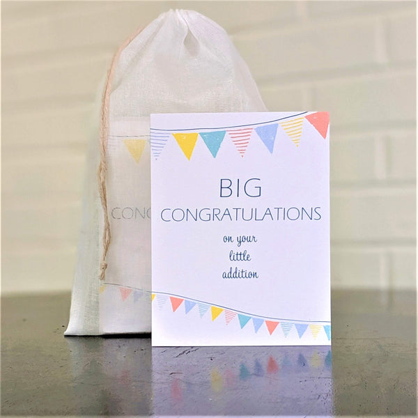 """Big Congratulations on your little addition"" greeting card, single card in front of set in sheer cotton pouch."