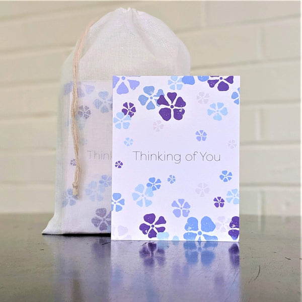 """Thinking of You"" greeting card with scattered flowers, single card in front of set"
