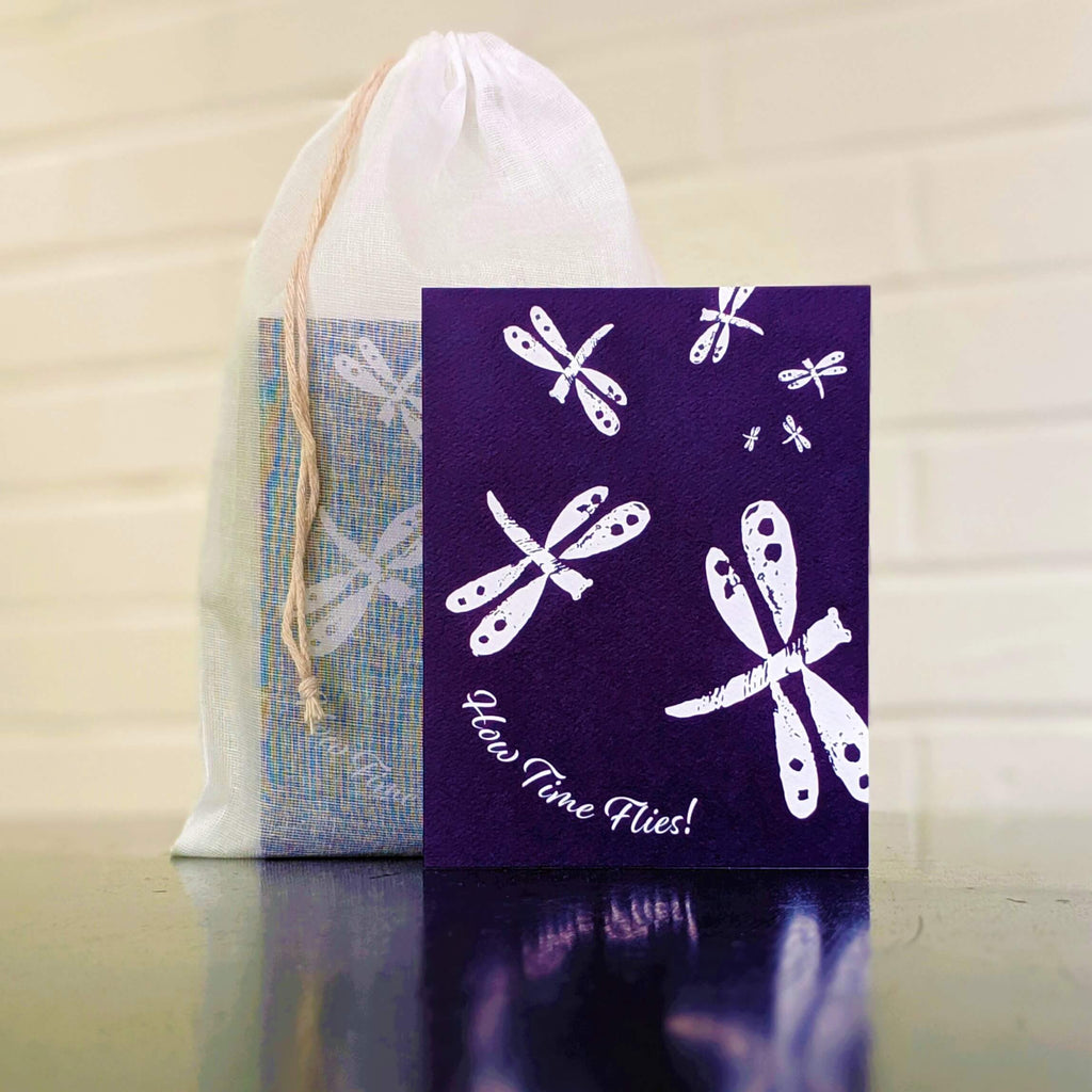 """How Time Flies"" dragonflies greeting card, single card in front of set in sheer cotton pouch"