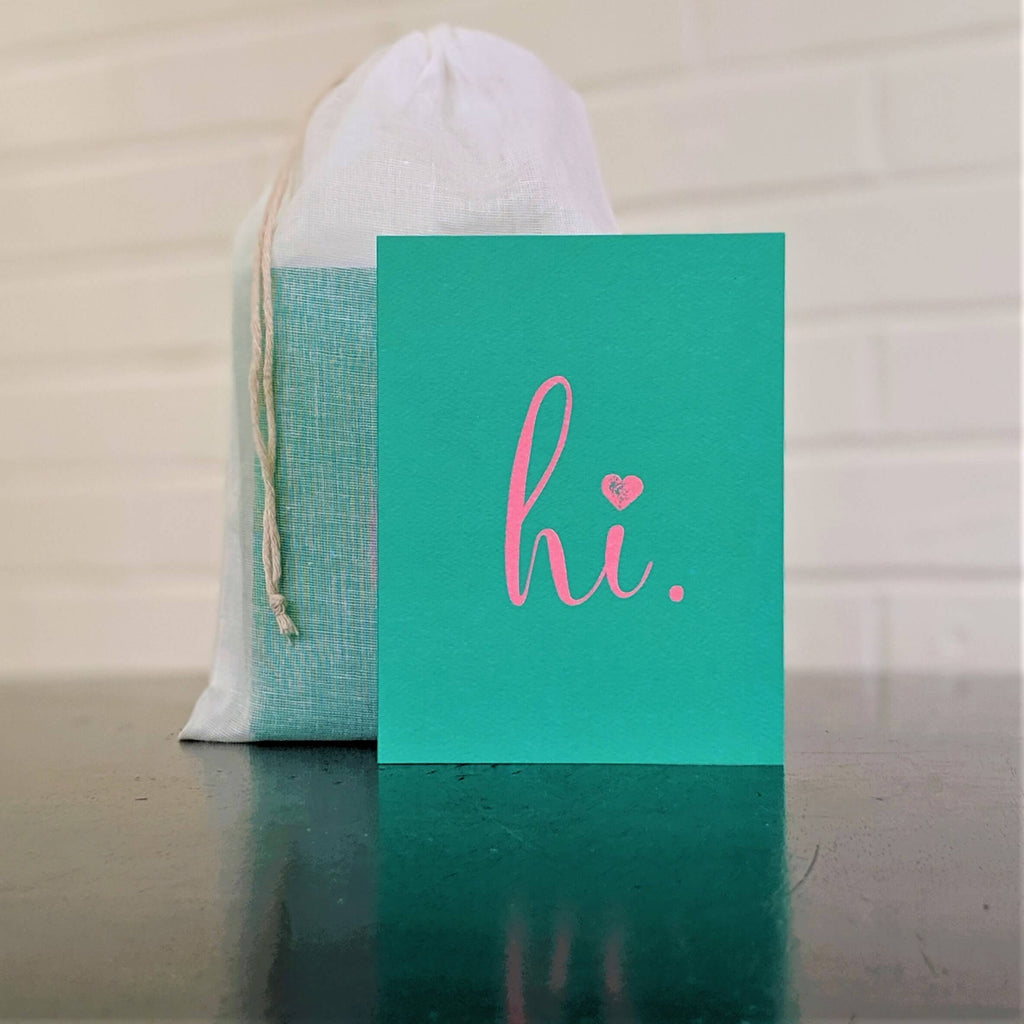 """hi."" card in green with pink, single card in front of set in sheer cotton pouch"