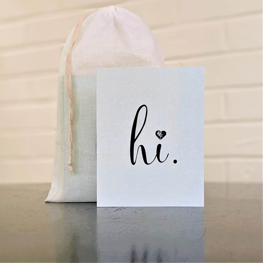 """hi."" greeting card in mint green with black, single card in front of set in sheer cotton pouch"