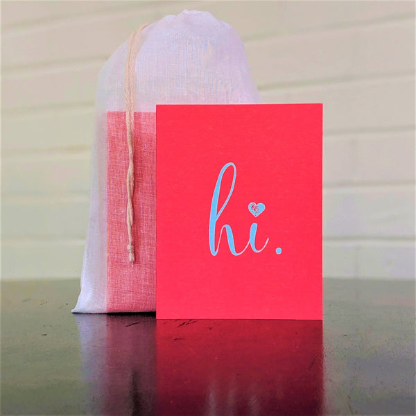 """hi."" greeting card in red with blue, single card in front of set in sheer cotton pouch"