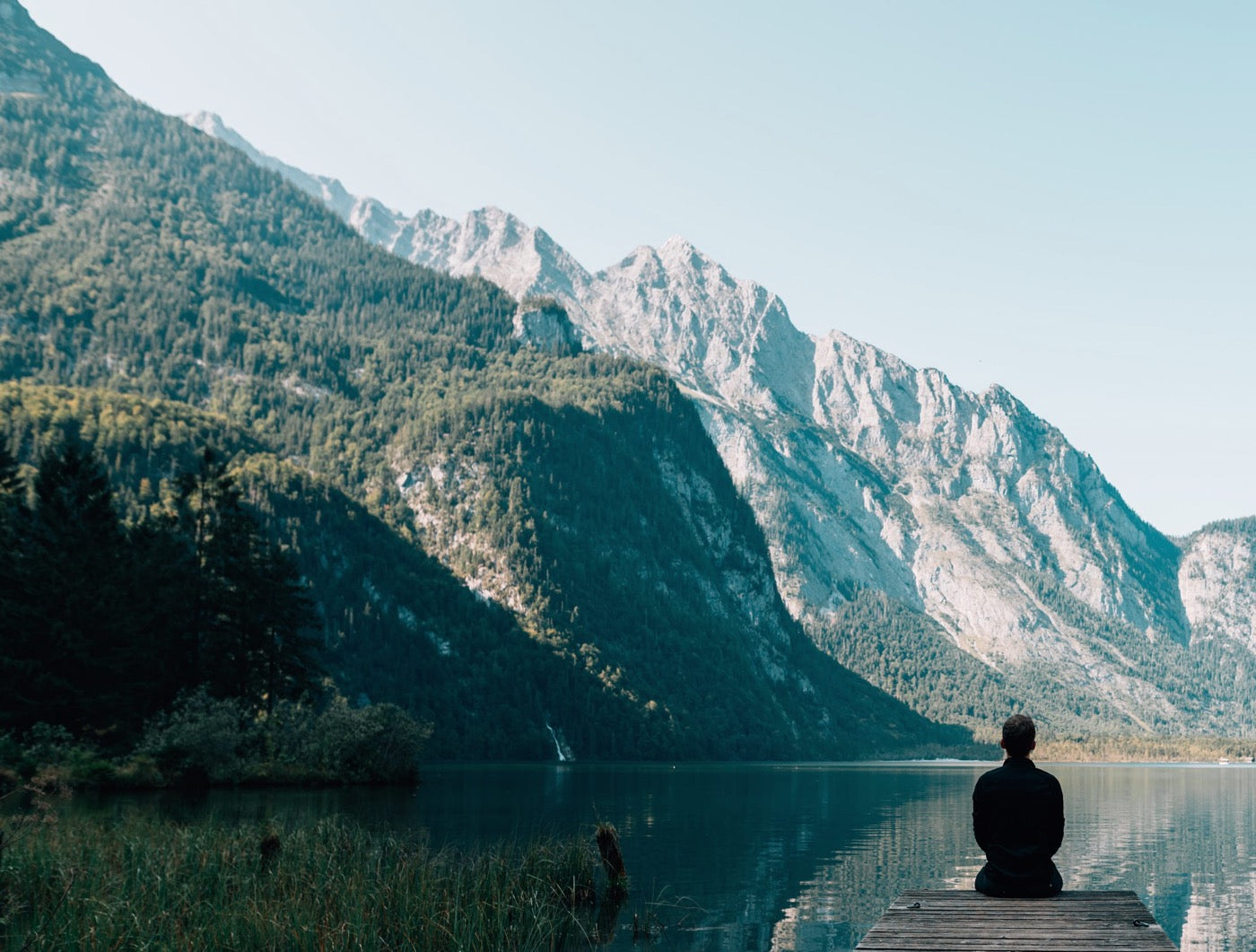 Person sitting quietly and overlooking a beautiful mountain lake