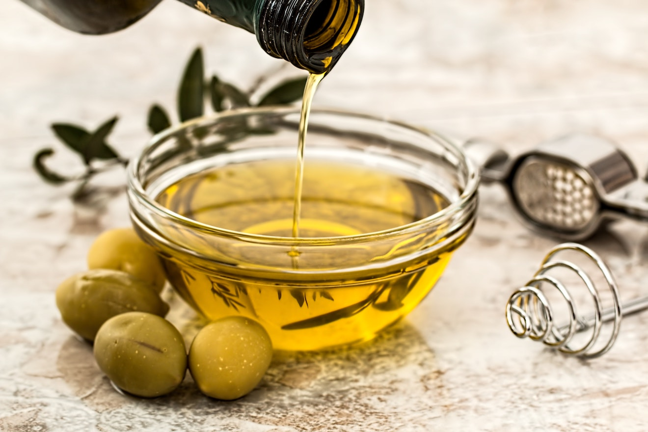 Small bowl of olive oil surrounded by olives