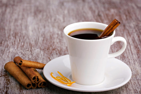 white cup with coffee and cinnamon sticks and orange skin, old wooden surface