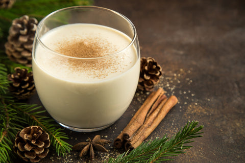 Traditional Christmas drink eggnog with grated nutmeg and cinnamon.