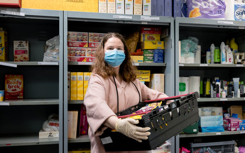 A volunteer at a Trussell Trust food bank wears gloves and face mask PPE in the coronovirus pandemic whilst packing a client parcel