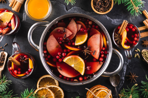 Top-down view of cooking pot of hot wine with aromatic spices on a black textured background. Christmas mulled wine. New Year's warming drink.