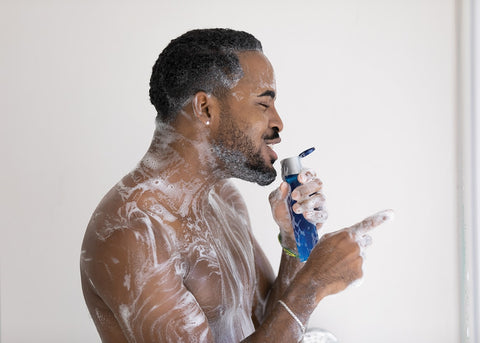 Smiling cheerful African American young man singing in shower, holding bottle of shower gel or shampoo, standing in bathroom at home, enjoying morning routine procedure