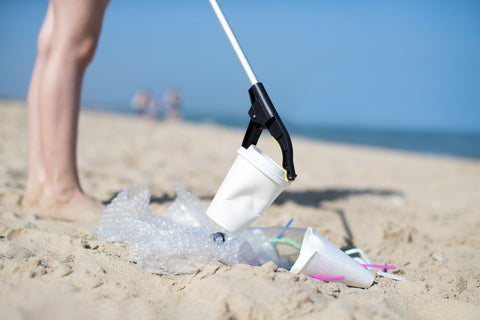 A man picking up a polystyrene cup from the beach