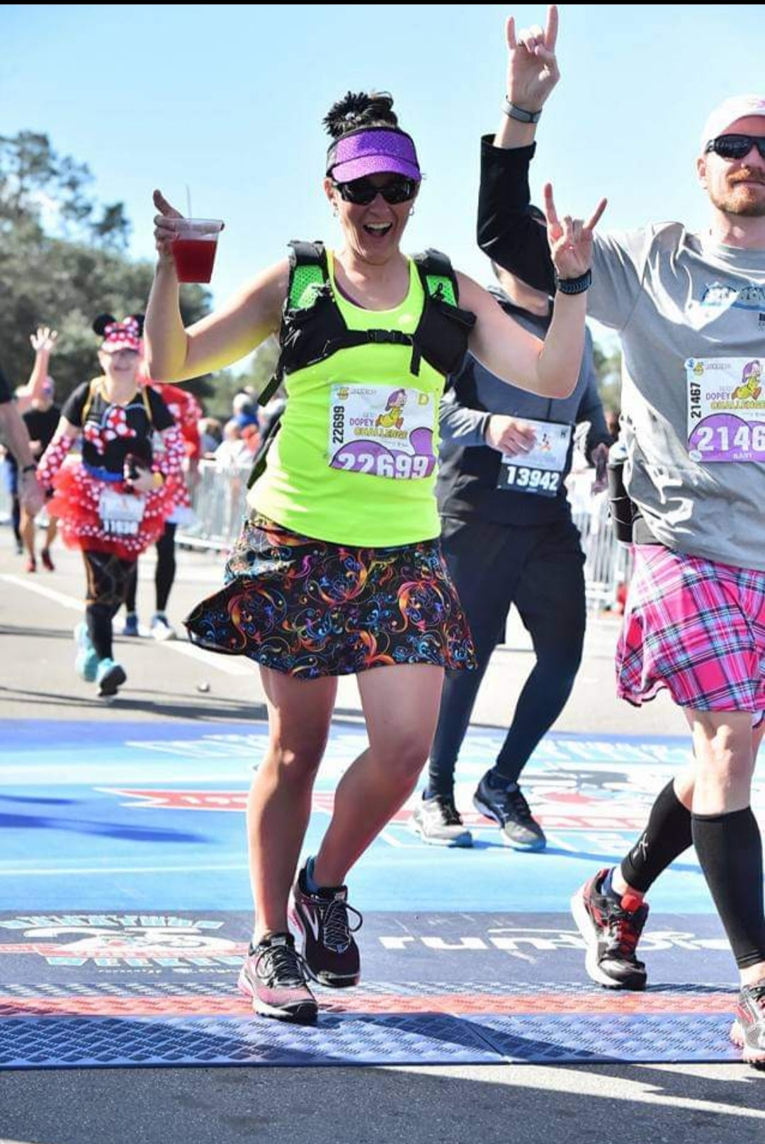 Melissa Marowelli finishing a race with drink in hand wearing a Bolder Athletic Wear skirt