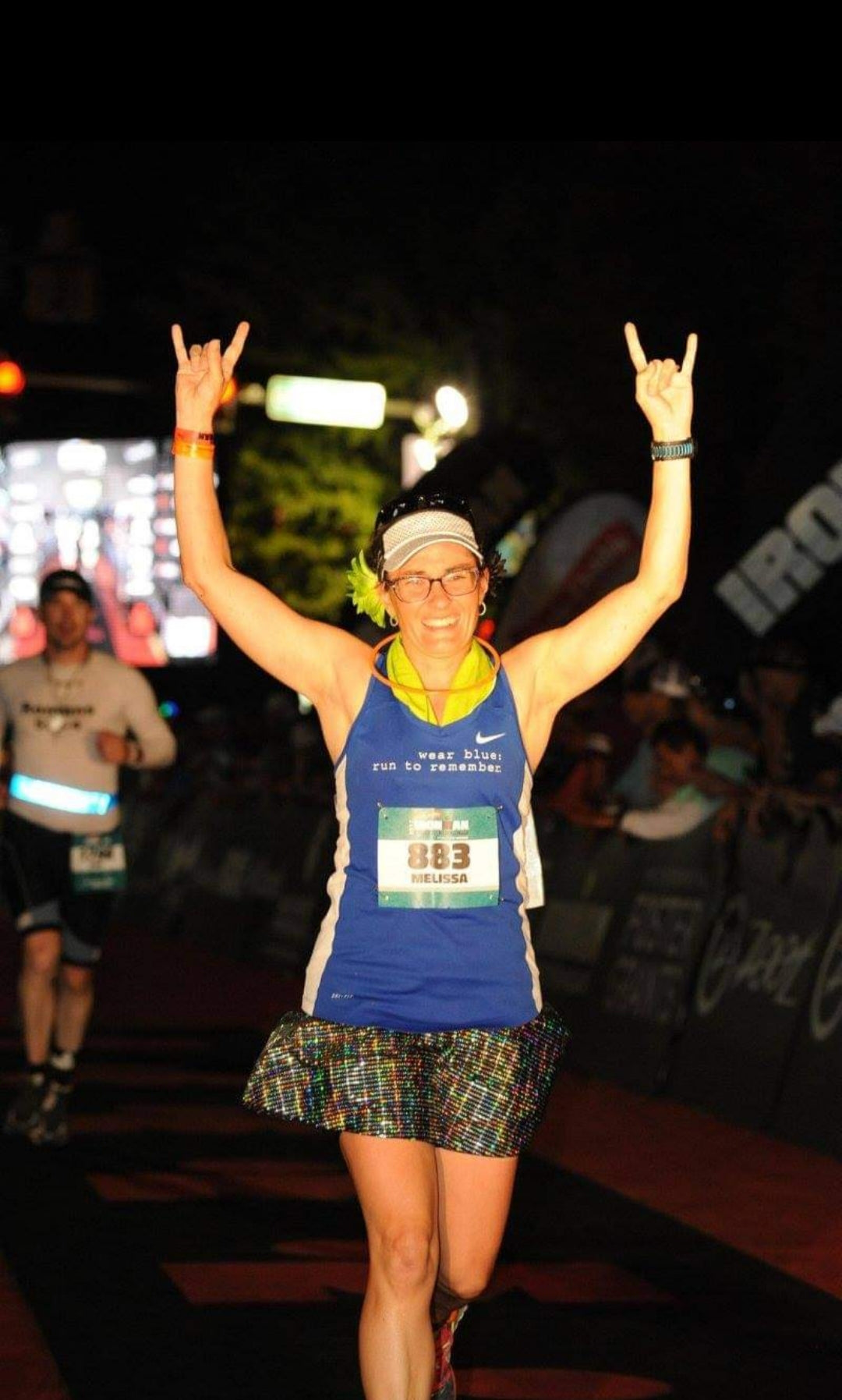 Melissa Marowelli smiling while finishing a race wearing a Bolder Athletic Wear skirt