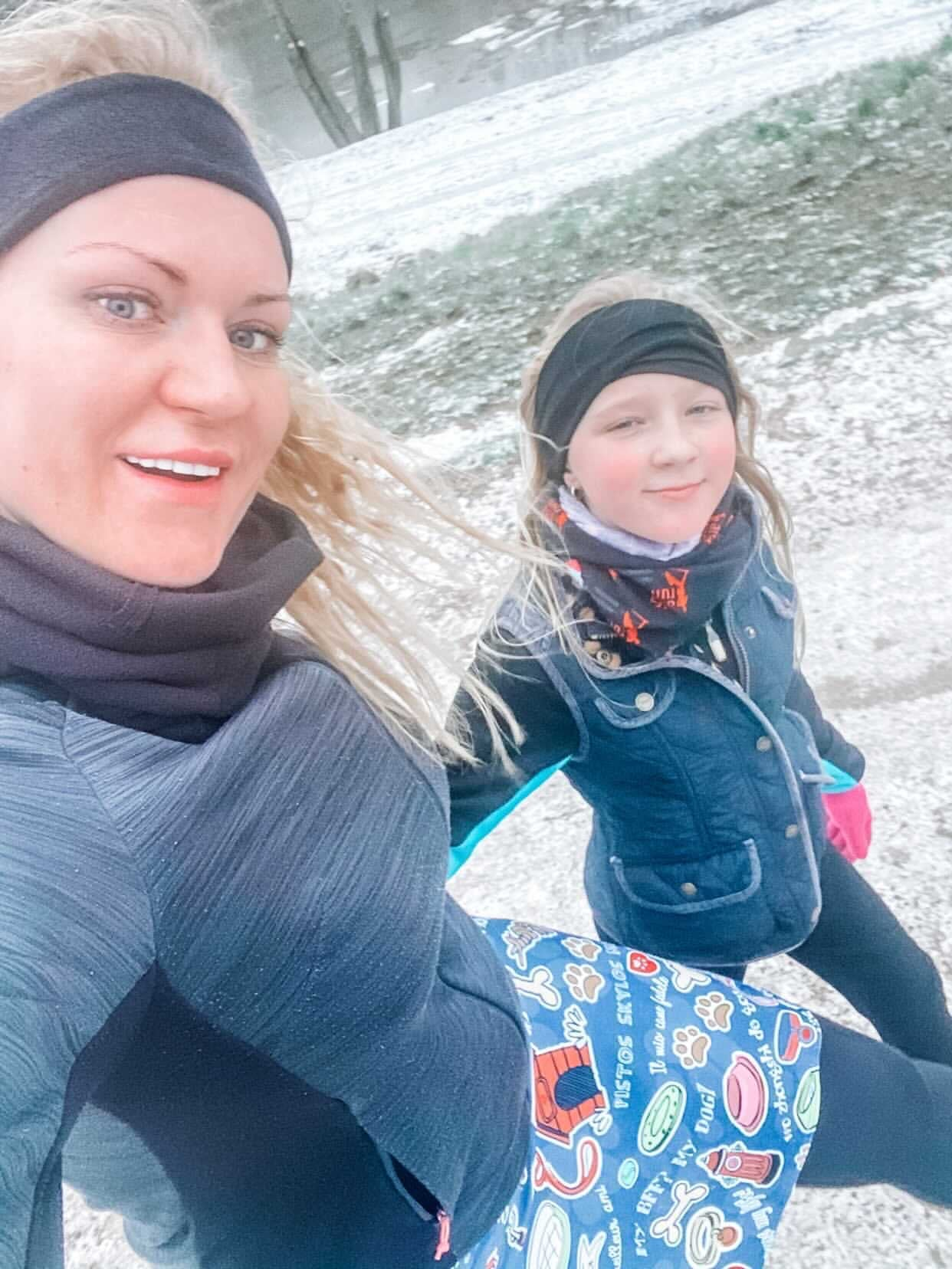 Samantha wearing a Bolder skirt with her child outside in the snow
