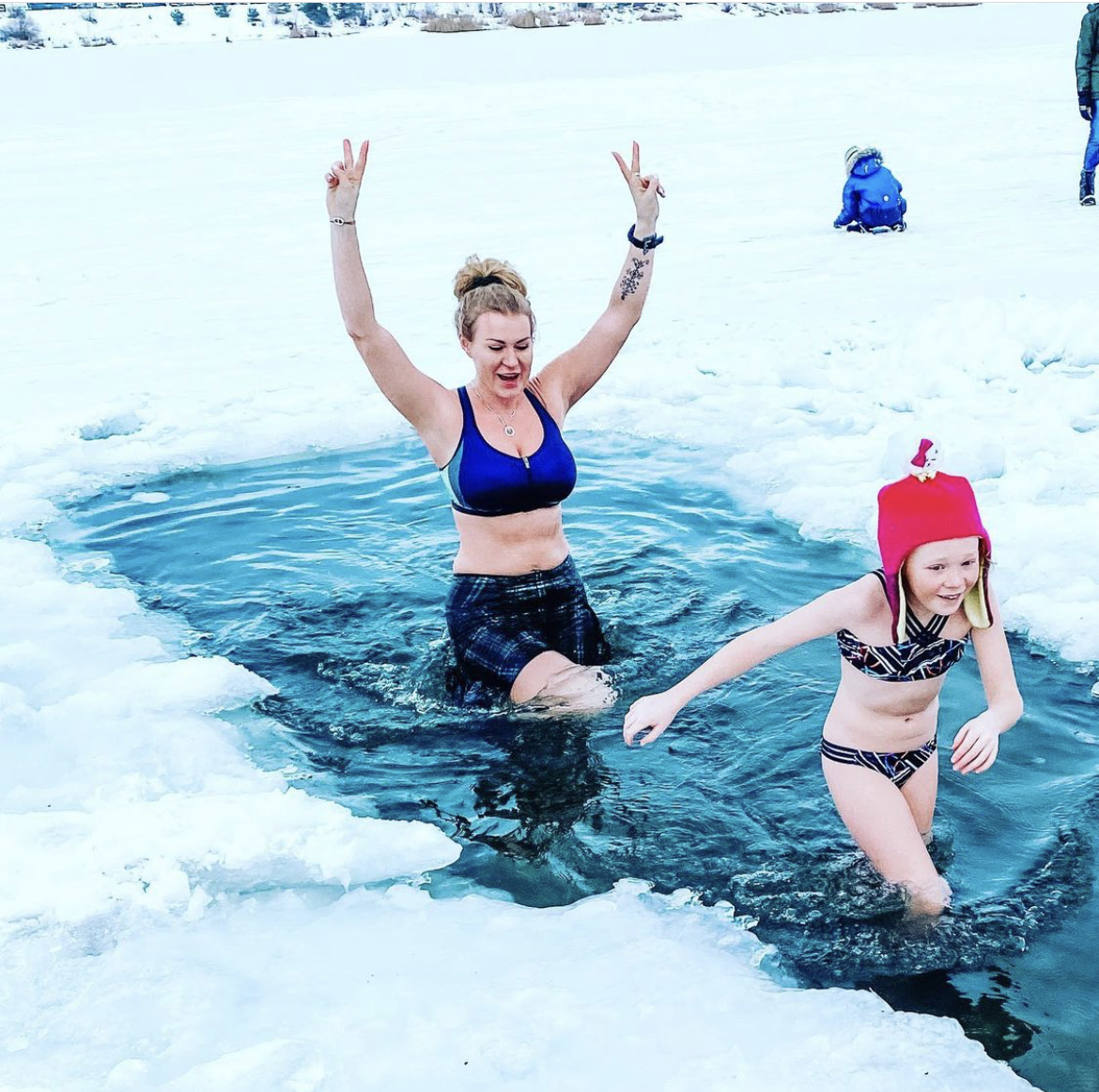 Samantha wearing a Bolder skirt in an ice hole with her child