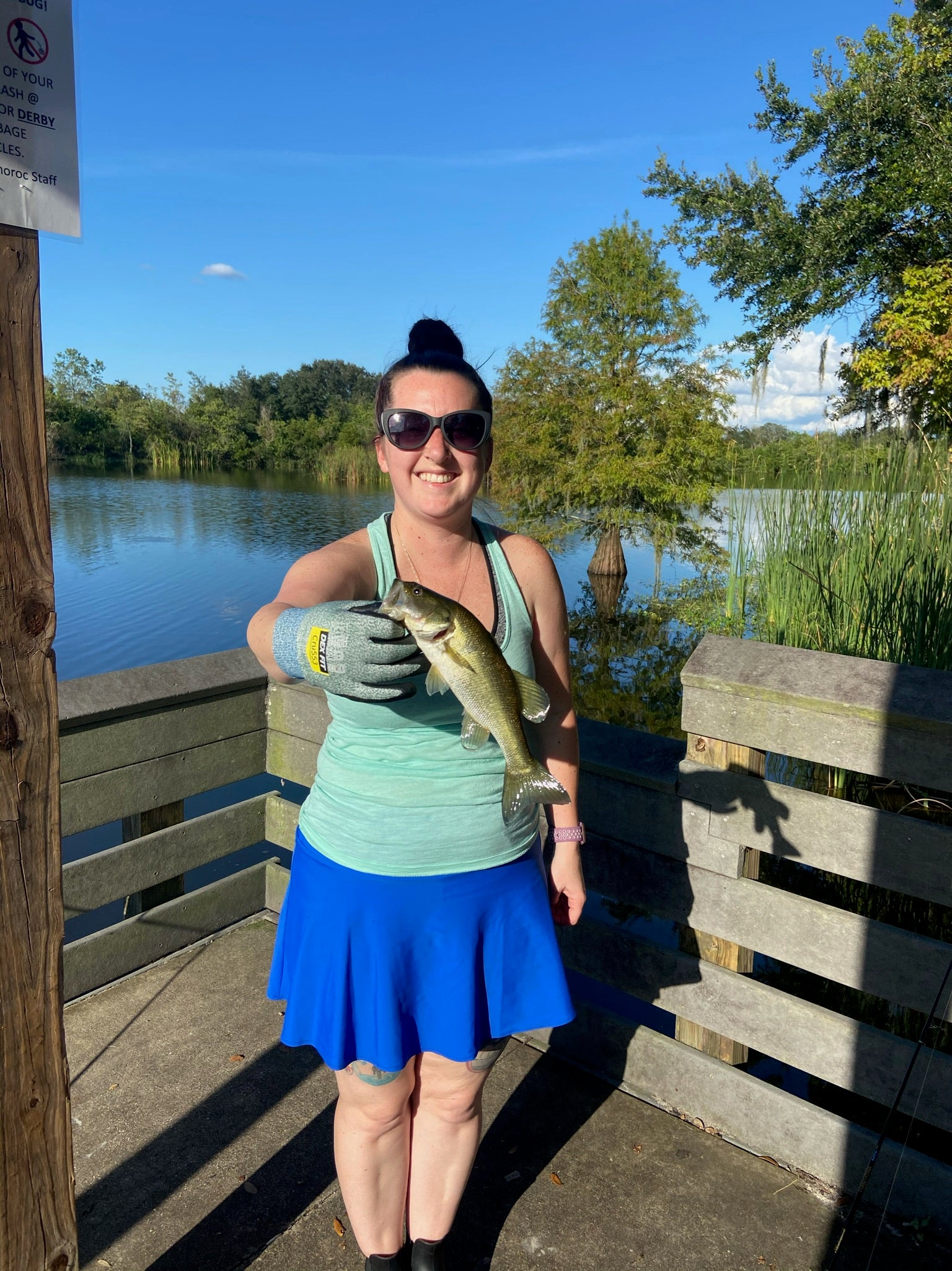 Becky on a dock holding a fish while wearing a Bolder skirt