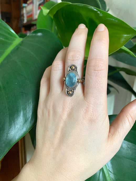 Sterling silver ring with oval aquamarine stone with brass spheres and silver arches on hand in front of plant.