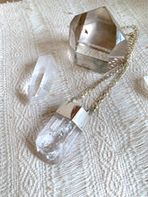 Load image into Gallery viewer, Danburite talisman necklace with sterling silver curb chain and setting next to quartz crystal and smoky quartz point on woven cloth.