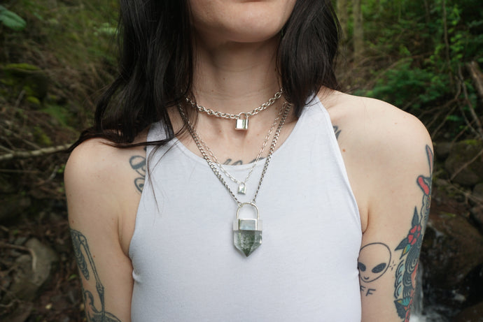Chlorite quartz talisman necklace with sterling silver curb chain and setting on dark haired girl with tattoos in the woods.