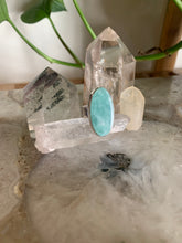 Load image into Gallery viewer, Oval Amazonite and sterling silver Ring on quartz crystal with crystal points and plant behind it.