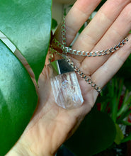 Load image into Gallery viewer, Danburite and sterling silver talisman necklace in hand with plant.